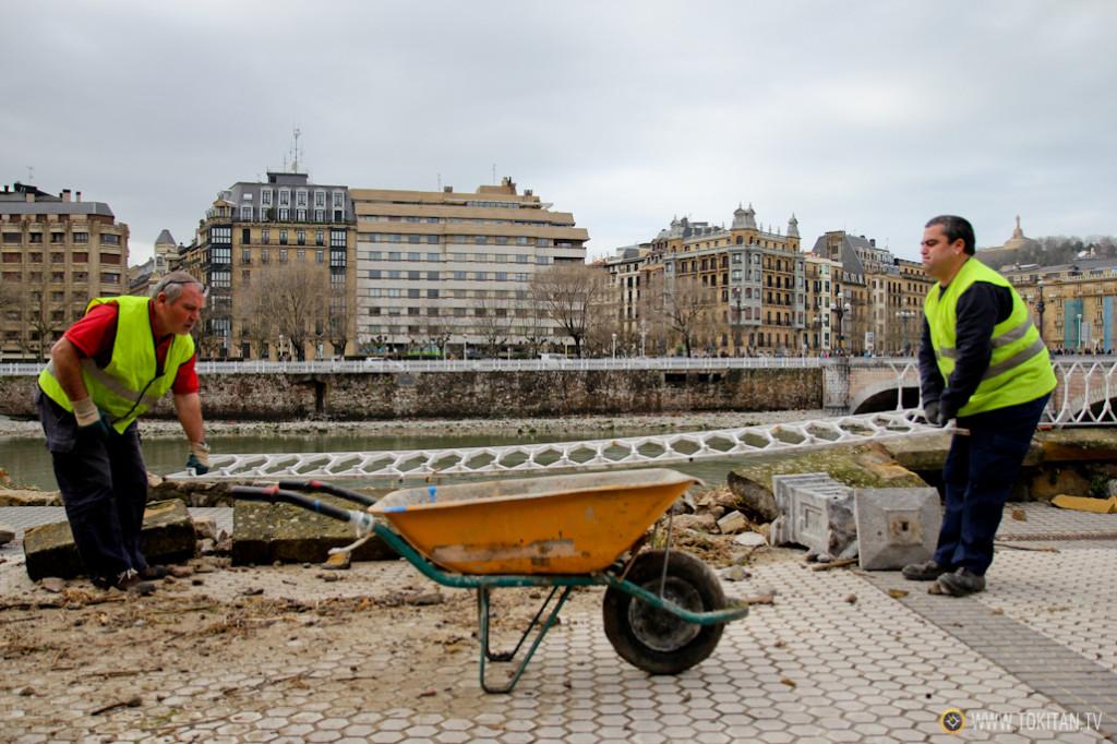 Operarios del Ayuntamiento de Donostia recogen los escombros causados por las olas.