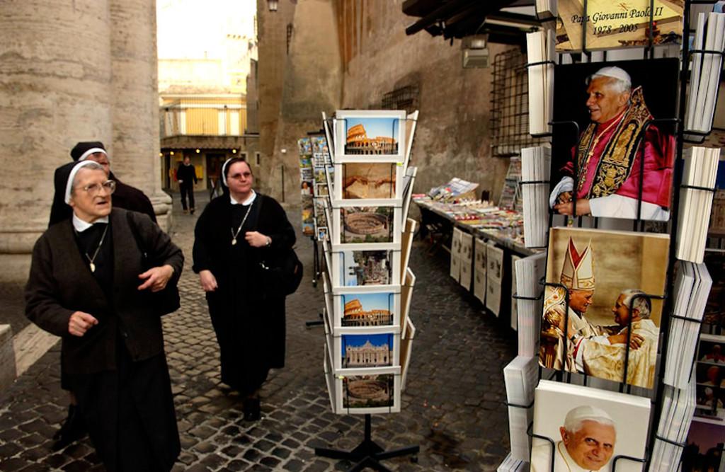 Un grupo de monjas pasa alrededor de una tienda de souvernirs en el Vaticano.