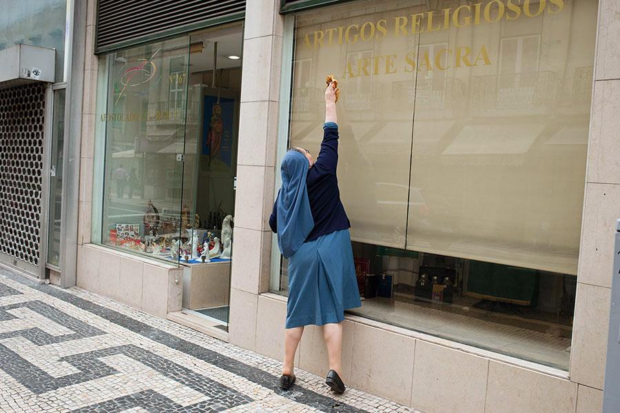 Una monja saca brillo al cristal del escaparate de una tienda de artículos religiosos y arte sacro. Cortesia de Rafa Pérez | Kamaleon Travel