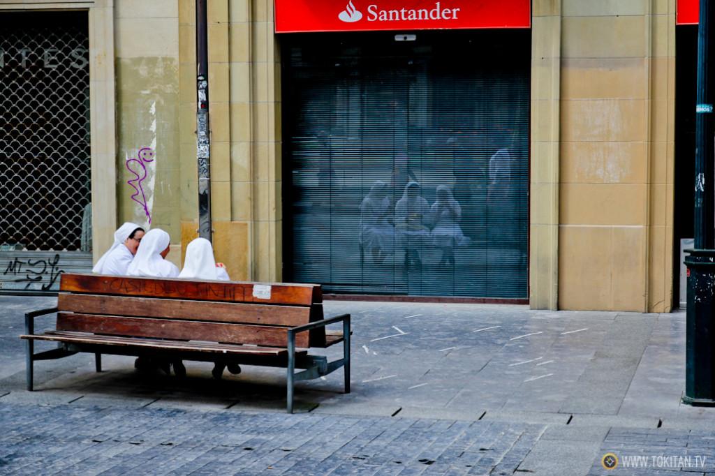 Tres monjas disfrutan de su helado en el Boulevard de Donostia, sentadas en un banco frente a otro.