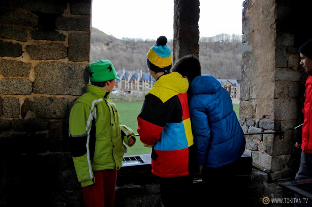 Un grupo de niños, con sus coloridas prendas de esquí, observan desde el campanario de la Iglesia de Saint Climent de Taüll.
