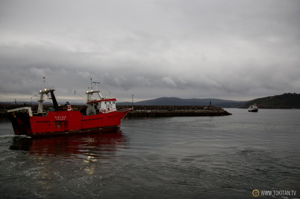 Un barco sale del puerto pesquero de muxía mientras otro regresa de faenar.