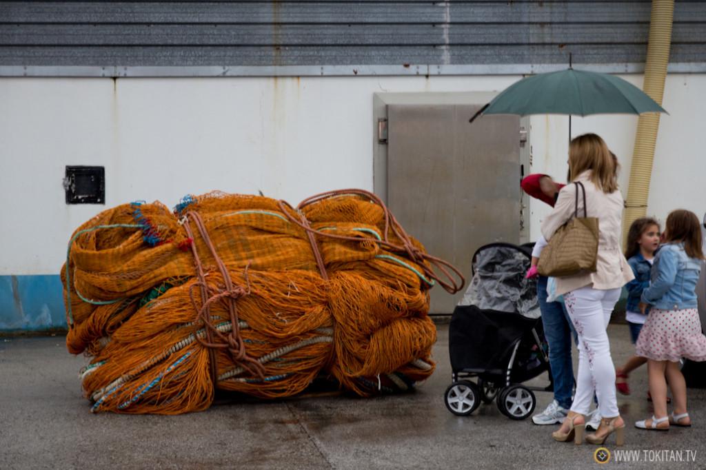 las familias aguardan a que se descargue el pescado para regresar a casa.