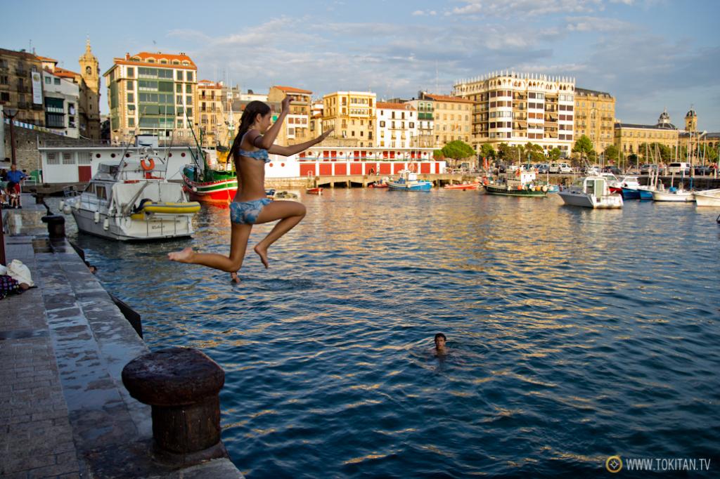 Una niña salta desde el muelle del puerto de Donostia durante las mareas vivas.