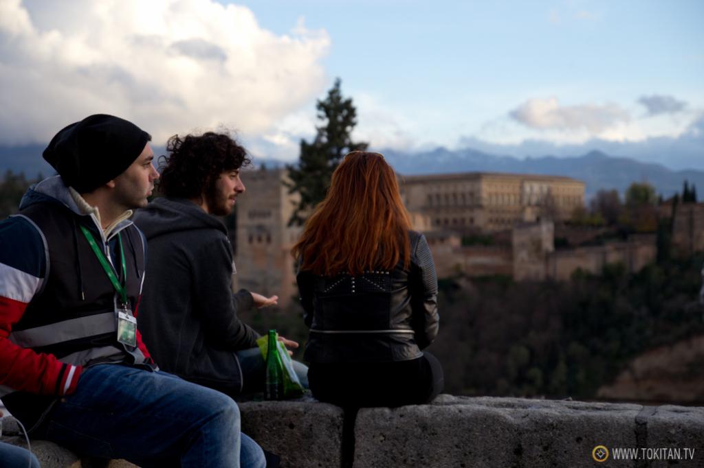 Turistas y locales comparten el pretil del mirador de San Nicolás mientras el sol se pone.