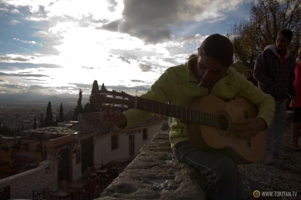 Uno de los músicos flamencos afina su guitarra al borde del mirador de San Nicolás.