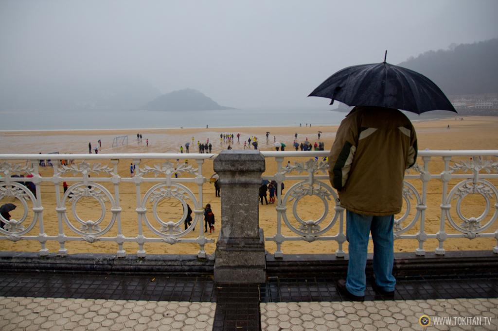 Un hombre observa la bahía de La Concha desde su característica barandilla.