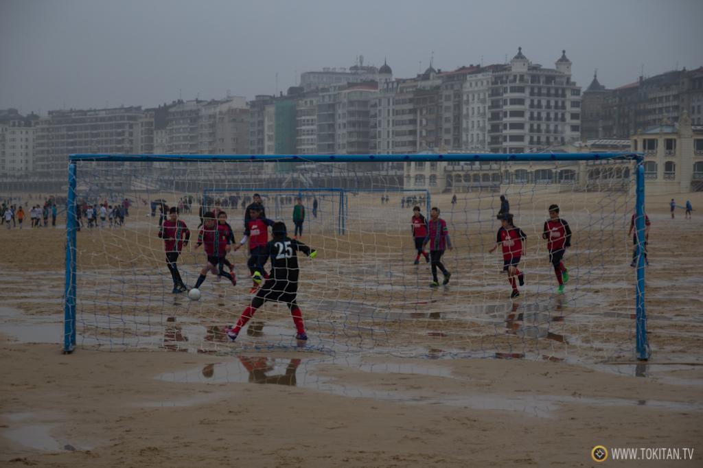 Los chavales y chavalas aprovechan para jugar al fútbol playa durante la bajamar.