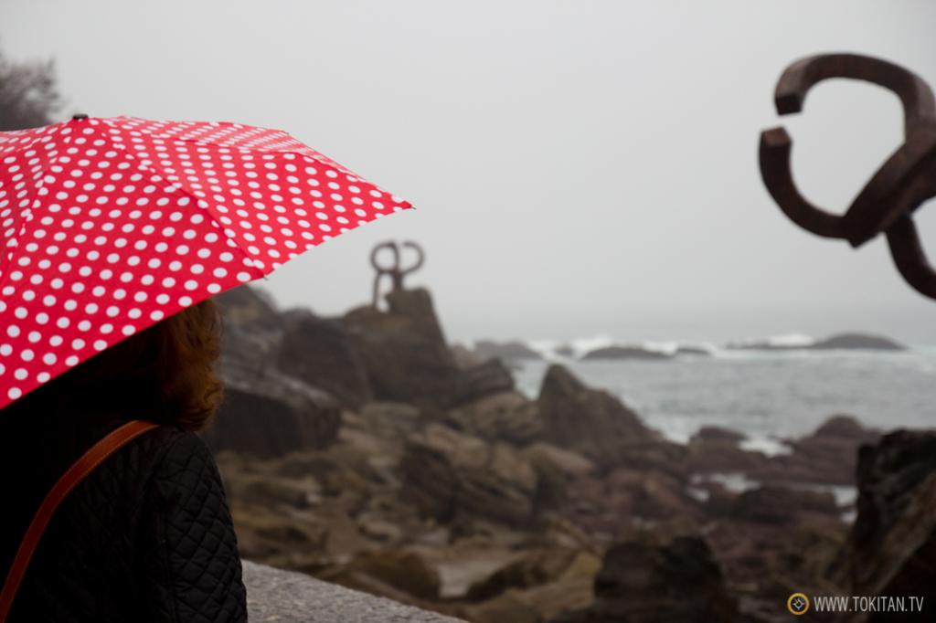 Una mujer observa el Peine del Viento. Cuánto juego dan los paraguas en la fotografía.