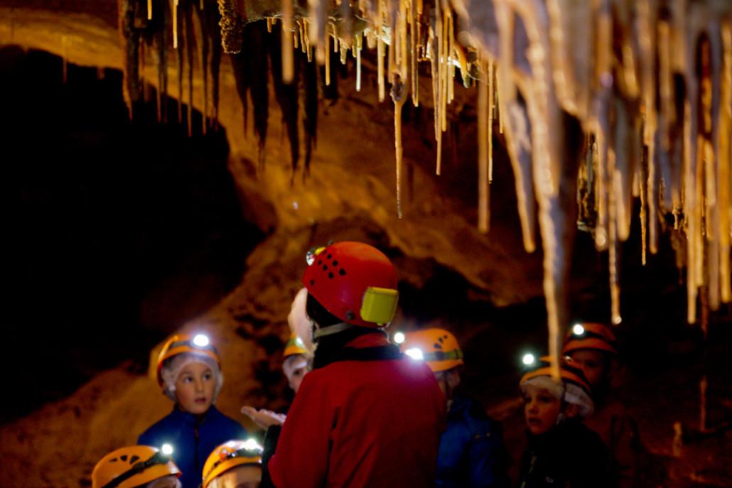 Los niños atienden a las explicaciones de la guía durante una visita Espeleotxiki.