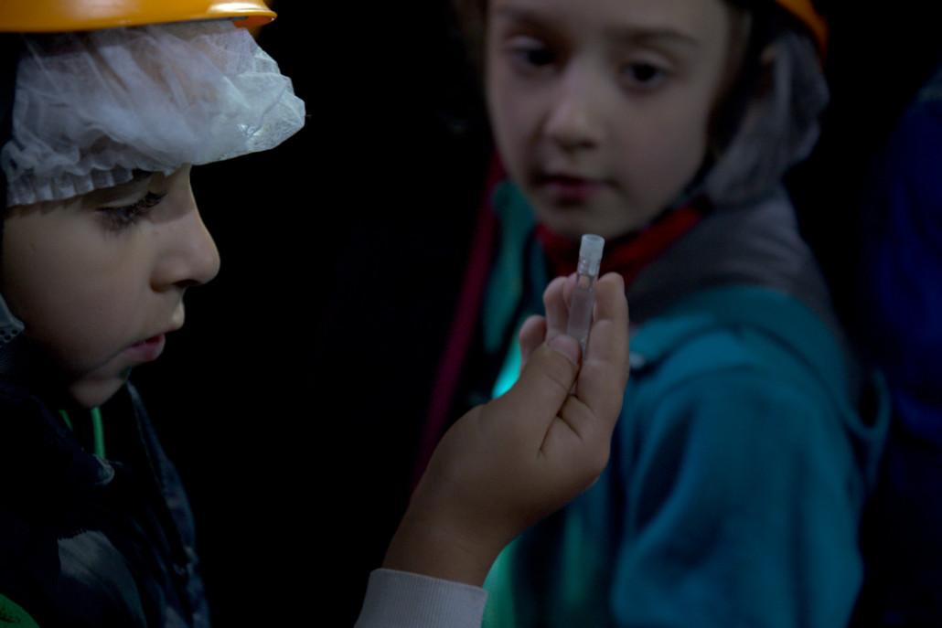 Los niños observan las muestras de organismos vivos de la cueva.
