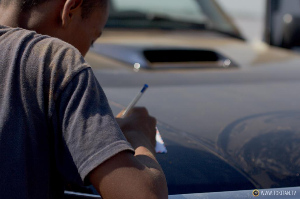 Un niño aprovecha el viaje en transbordador para escribir una carta.